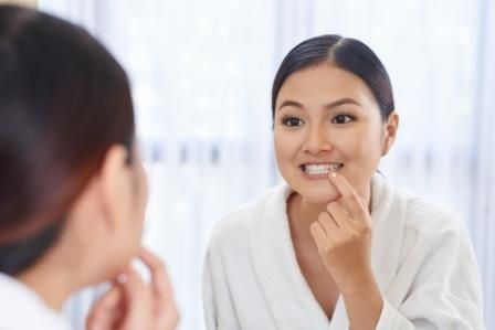 Edmonton woman looking at her gums in the mirror
