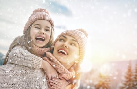An Edmonton woman and her child enjoying winter weather with bright white smiles